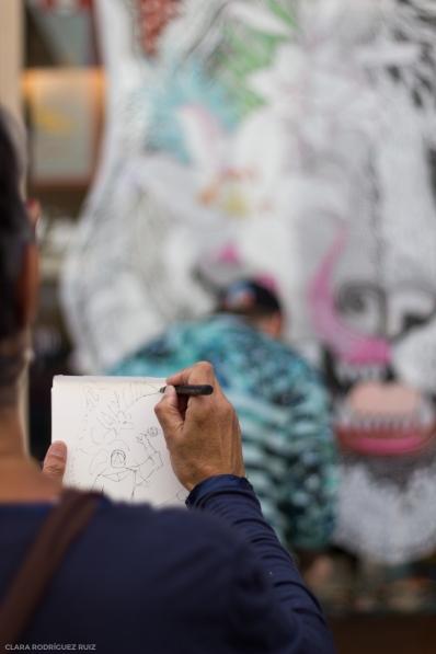 """Mujer dibuja al artista """"El dios de los tres""""."""